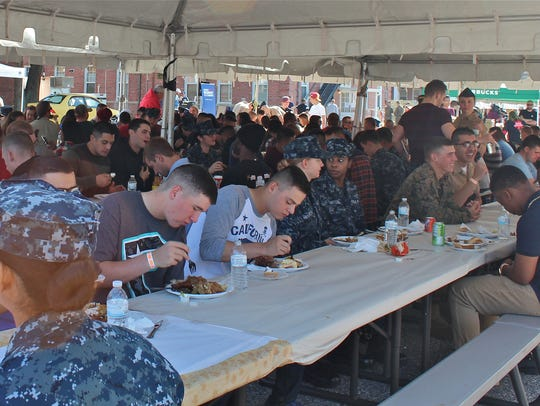 Hundreds of military service members sit together for