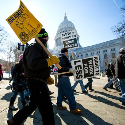 Protesters march around the state Capitol in Madison