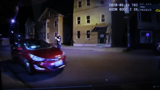 A still from body camera footage shows a Providence police officer, Matthew Sandorse, approaching a red sedan. Inside were a Providence firefighter, Terrell Paci, and another person.