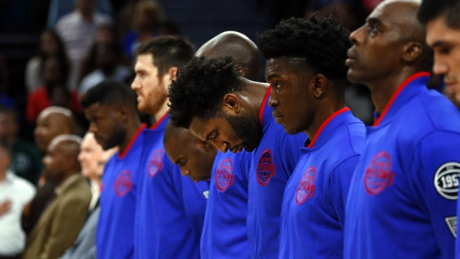 Pistons center Andre Drummond, middle, lowers his head during the national anthem before a game last season.