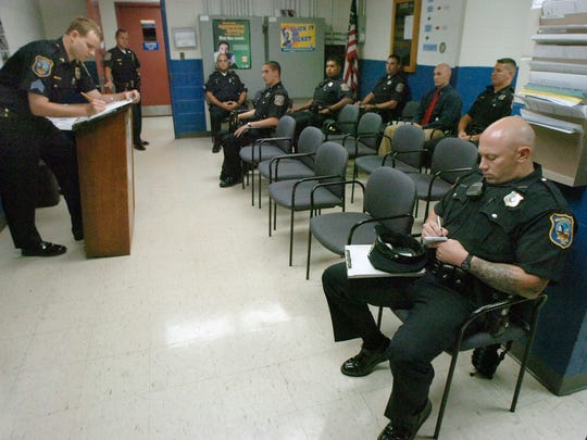 Then-Sgt. Stephen Misetic, left, performs the morning roll call at the Wilmington Police Department in 2007. Patrolman Thomas Kavanaugh takes notes during the brief meeting while Patrolman Daniel Vignola, center, listens.