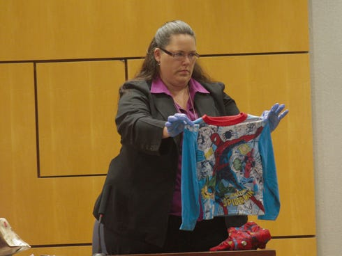 A Titusville, Fla., police investigator in court on Wednesday, Jan. 8, 2014, held up the tiny Spider-Man pajamas a boy was wearing when he was found after he said he was locked and starved by his father and his mate.