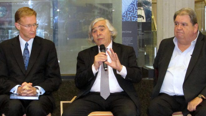 U.S. Energy Secretary Ernest Moniz, center, answers a reporter's question at Corning Inc. on Friday. Corning Inc. Chairman and CEO Wendell Weeks is on the left, and Thomas Conway, international vice president of the United Steelworkers union, on the right.