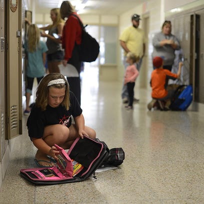 Olivia Shelly, 11, puts supplies in her locker during