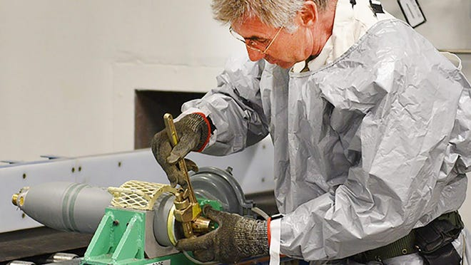 A Pueblo Chemical Agent Destruction Pilot Plant ordnance technician removes the rear assembly from a 4.2-inch mortar round.