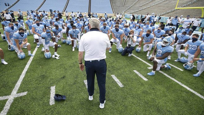 North Carolina coach Mack Brown meets with the Tar Heels after their victory against Syracuse in the Sept. 12 season opener.