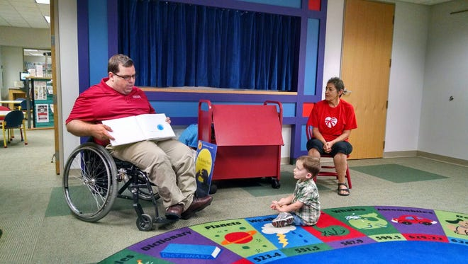 Reporter Tim Engstrom reads to Michael Goff, 3,  at East County Library for Make a Difference Day.
