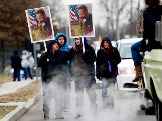 Parade members carries signs during the annual MLK