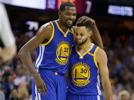 Kevin Durant hugs teammate Stephen Curry during the