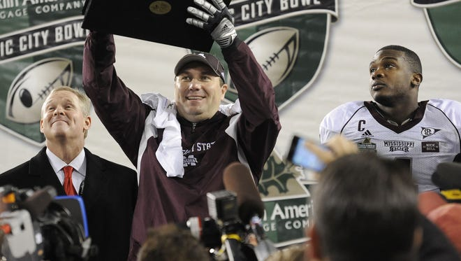 Mississippi State Bulldogs head coach Dan Mullen holds up the trophy after his team defeated Wake Forest 23-17 in the Franklin American Mortgage Company Music City Bowl at LP Field Friday Dec. 30, 2011 in Nashville, Tenn.