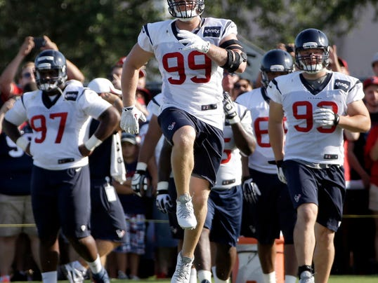 """FILE - In this July 27, 2014 file photo, Houston Texans defensive end J.J. Watt (99) stretches with teammates during an NFL football training camp practice in Houston. Watt knows it's cliche to say """"we're working hard every day"""" and he's """"just trying to be a good teammate.""""(AP Photo/David J. Phillip, File)"""