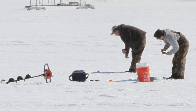 A pair of ice fishermen work their holes on Lake Chemung in Genoa Township during an outbreak of unseasonably warm temperatures this week.