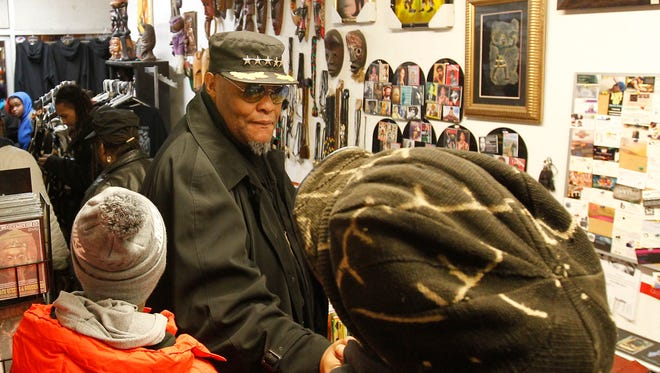 King Rick, a Milwaukee Black Panther member thanks the shop owner at the Pursonality gift shop Wednesday. Milwaukee Black Panther members are shopping at Pursonality at Silver Mill Plaza and a few other area stores for gifts for five families who lost loved ones due to violence in 2016.
