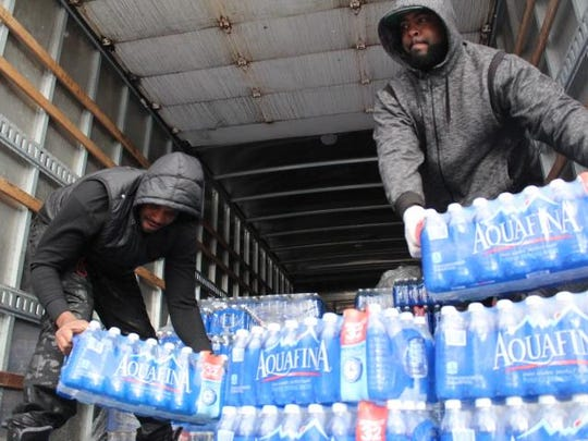 Negus Vu, vice-president of New Era Detroit, and Zeek, president of New Era Detroit, distribute water to Flint residents on Jan. 17, Sunday.