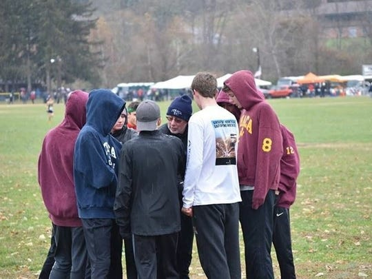 Rich Bernstein huddles with members of the Ithaca cross country team.