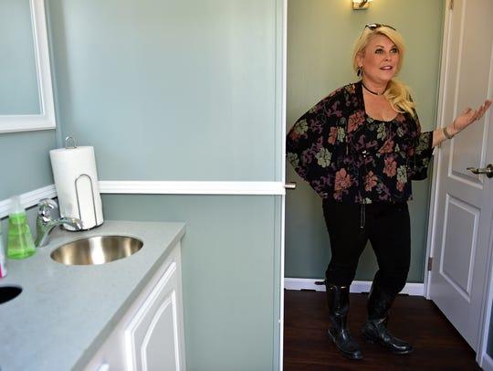 Lauren McGraw stands in one of her mobile restrooms