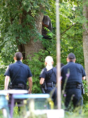 Fond du Lac police wait for a man they were chasing to climb down from a tree Tuesday, Aug. 1, 2017, in the 200 block of Amory Street in Fond du Lac.