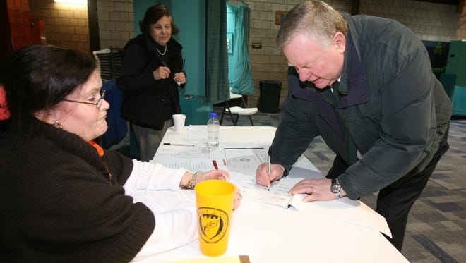 Acting Village Judge Michael O'Toole, signs the election register as he prepares to vote in the Village of Tuckahoe elections at the Tuckahoe Community Center, March 18, 2014. Looking on are election inspectors Virginia Marciano and Adelaide DiGiorgi.