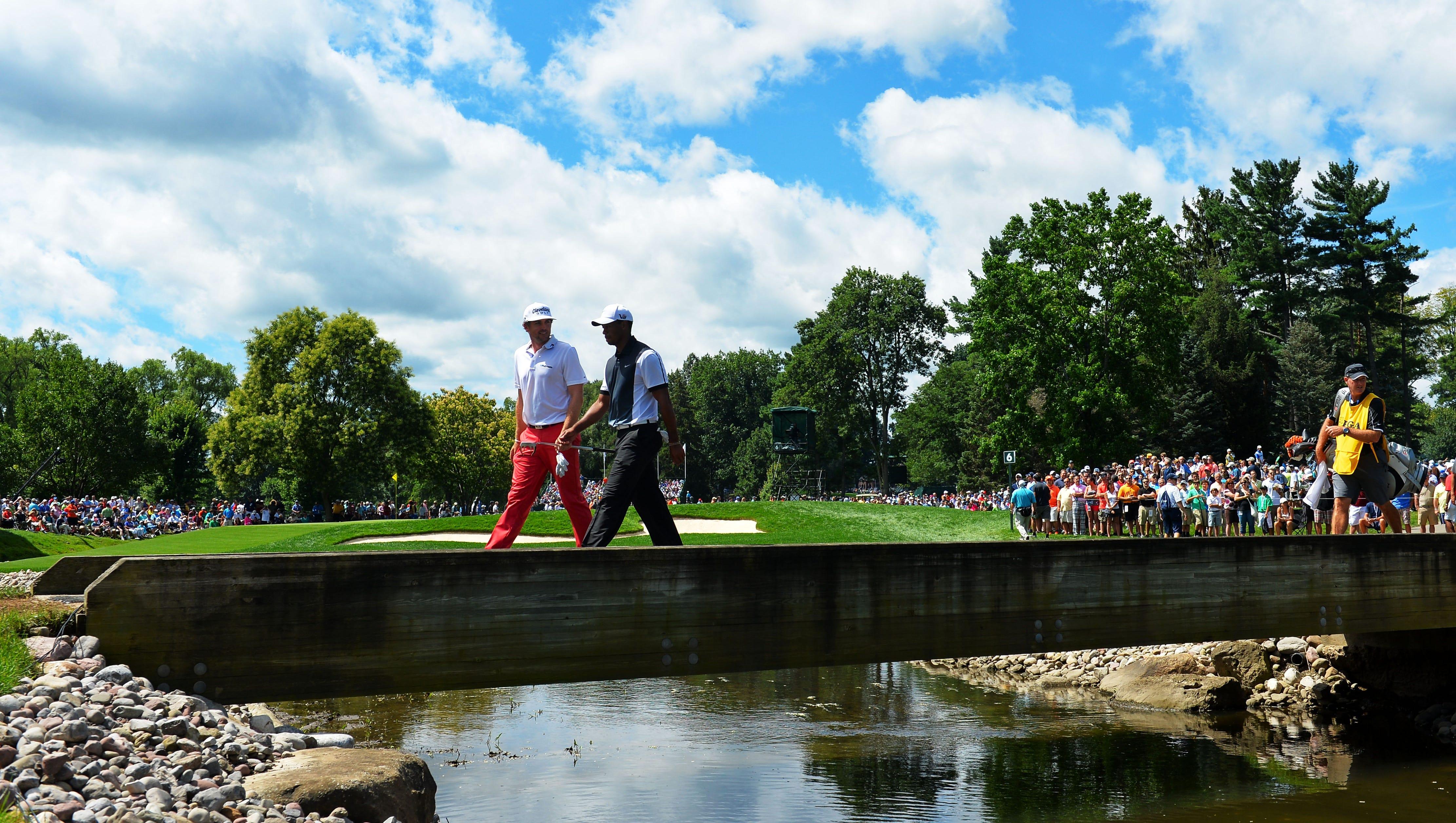 Keegan Bradley and Tiger Woods cross a bridge on the sixth hole.