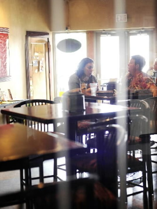 Lauren Nicholl of York, left, and Eve Thorr of West York have drinks Friday at Flats in York. The café serves draft beers, wine and specialty sangria, along with nonalcoholic fresh-brewed teas.