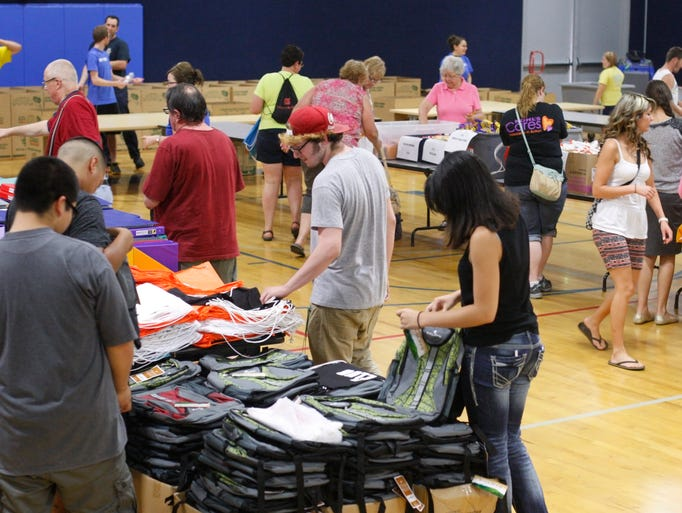 Volunteers stuff 1700 backpacks with school supplies at the Knudson Boys & Girls Club on Thursday, July 31, 2014. The backpacks will be given out to children in need next week.