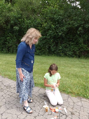 Glenda Ritz asks Lucy Engle about her lunch Friday at the Just Us Kids Outdoors program at Middlefork Reservoir.