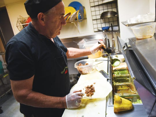 Bob Cook, owner of Queso Dee'as cooks up a meal at
