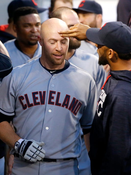 Cleveland Indians' Danny Salazar, right, wipes the sweat from the forehead of Chris Gimenez after Gimenez's home run off Chicago White Sox starting pitcher Chris Sale during the fourth inning of a baseball game Tuesday, May 24, 2016, in Chicago. (AP Photo/Charles Rex Arbogast)