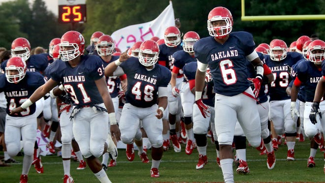 Oakland's Josh Smith Anthony Akers and Kyle Oliver take the field with the football team before the Oakland vs. White Station game at Oakland, on Friday,  August  29, 2014.