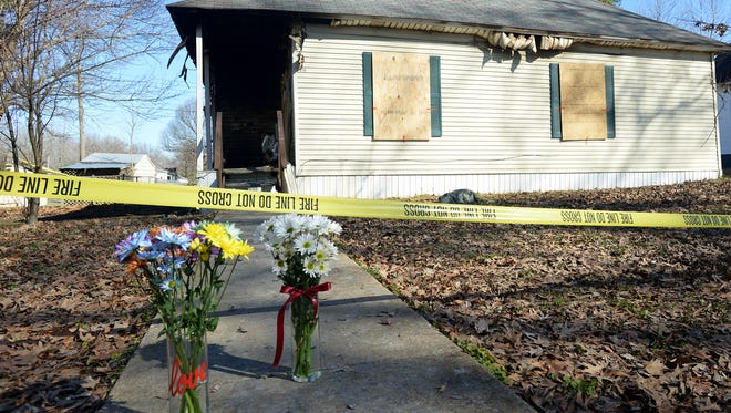 Flowers are set outside of the home at 214 B St. in Bemis on Thursday. Two adults and one child died in a fire at the home Wednesday morning.