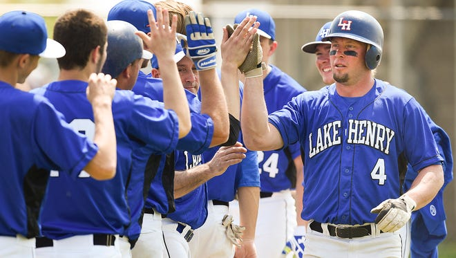 Lake Henry's Josh Kampsen (4) is met by teammates after scoring on a home run during the fourth inning Sunday, May 8, in Richmond.