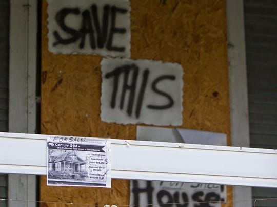 Signs and flyers outside of the home at 617 New York Street Friday, September 12, 2014, in Lafayette. The Lafayette Hearing Authority on Tuesday, Sept. 9,  postponed a vote to place the house on the unsafe structures demolition list, creating more time to find a buyer.