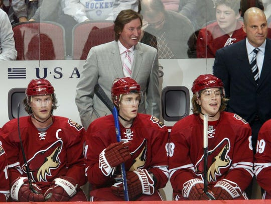 Wayne Gretzky and Rick Tocchet stand behind the Coyotes