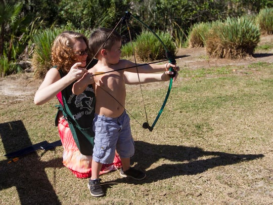 Case Bodiot, 3, learns to shoot a bow and arrow with the help of Kathleen Ramey at the 21st Annual Medieval Faire Saturday at Lakes Park in south Fort Myers. The event continues on Sunday and next weekend.