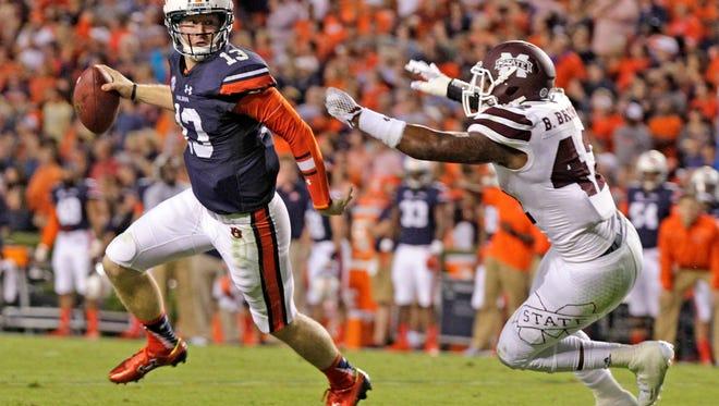Auburn quarterback Sean White (13) scrambles away from Mississippi State linebacker Beniquez Brown (42) during a 2015 game at Auburn.