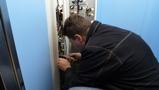 A mechanic repairing an elevator.