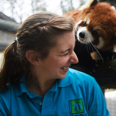 Zookeeper Robyn Melechinsky smiles as a Red Panda searches