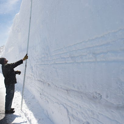 Todd Greer takes a measurement of a 19-foot snow drift