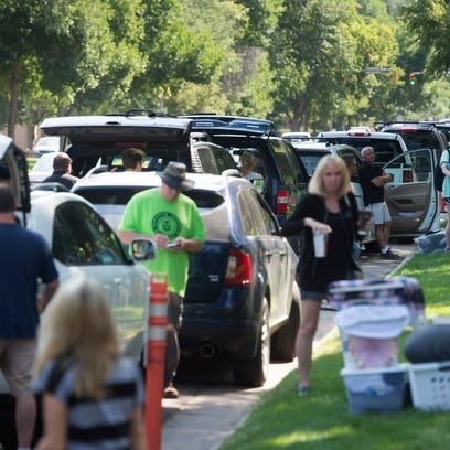 Parents, students and volunteers unload vehicles on