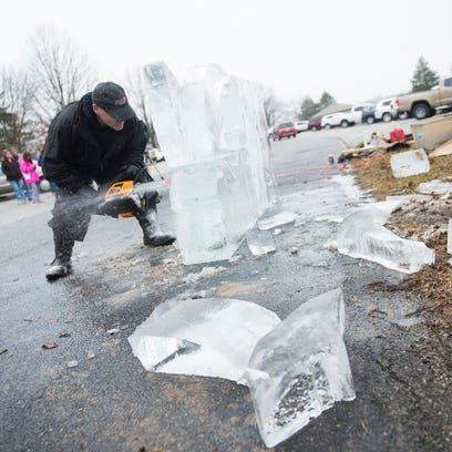 Bruce Keefer uses a chain saw to create an ice sculpture