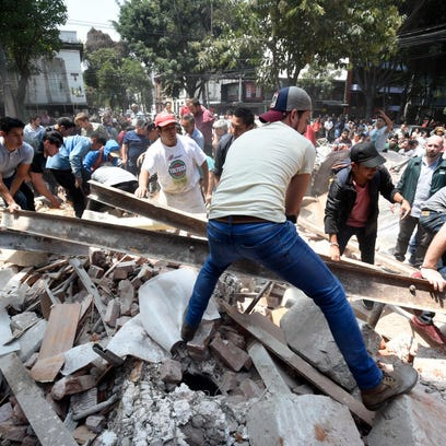 People remove debris of a building which collapsed