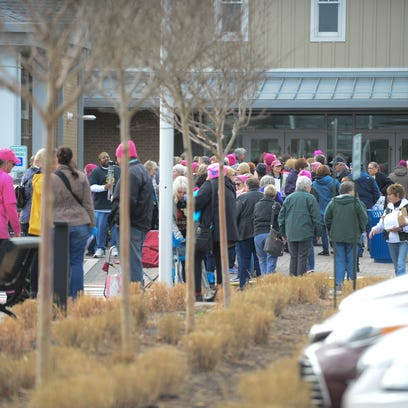Individuals gather outside of the Lewes Library on