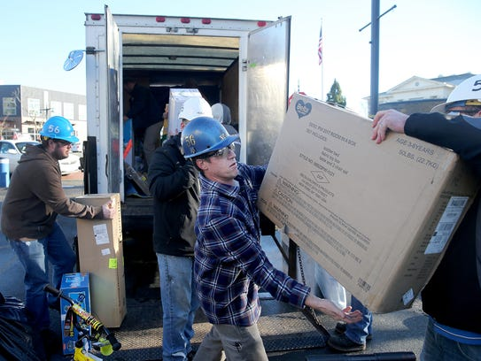 Shop 56 worker Greg Noah helps to load a KCR van with