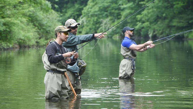 "Veterans William ""T.J."" Spiak Jr., left, and Marc Coviello, right, go fly fishing in Wappinger Creek near Route 44 in Pleasant Valley. This outing is part of the 1st Annual Weekend for Warriors, a weekend-long event honoring four local veterans. With them is John Carpenter, center, sporting adventures support from Orvis."