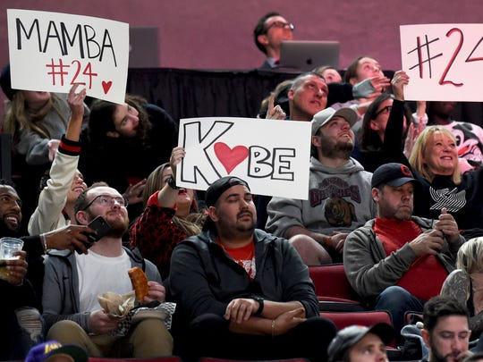 Fans hold up signs in memory of Kobe Bryant, who was killed in a helicopter crash in California, during the second half of an NBA basketball game between the Portland Trail Blazers and the Indiana Pacers in Portland, Ore., Sunday, Jan. 26, 2020. The Blazers won 139-129. (AP Photo/Steve Dykes)