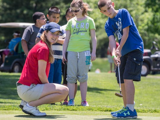 Jordan Britt gives Dakota Dunn some putting tips as part of a Symetra Tour FireKeepers Championship Kids Clinic earlier this week at the Battle Creek Country Club.
