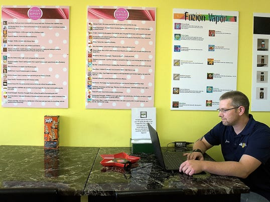 """SS Vape Diustrict Manager Jason Goins looks up a product for a customer under vape product advertising in the store at Manchester Crossroads shopping center Thursday, July 2, 2015. He says that vaping helps people quit smoking, which he did 3 1/2 years ago by vaping. The store initials stand for """"stop smoking"""". Bill Kalina - bkalina@yorkdispatch.com"""