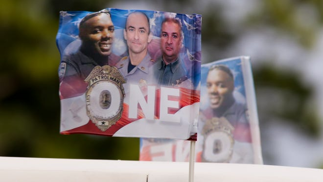 Flags showing the three Baton Rouge law enforcement officers killed in a July 17 shootout, fly on a limousine at the internment ceremony Monday of Cpl.  Montrell Jackson.