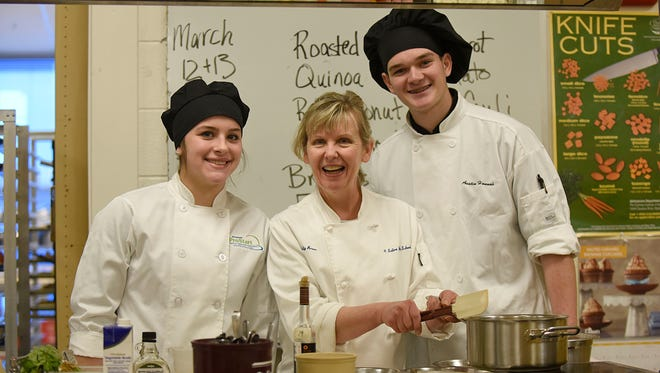 Chef Polly Brown poses for a photo with students Kelly Zielinski and Austin Hannah.