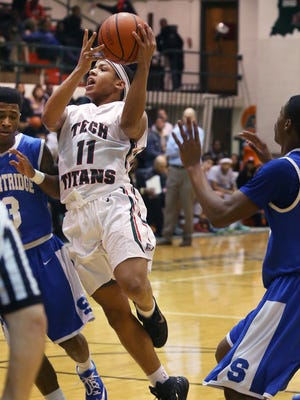 C.J. Walker, Arsenal Tech's leading scorer with 24 points, goes in for a layup against Shortridge Blue Devil Chris Adams, the game's high scorer with 28 points, during the Titans' 70-53 City Tournament quarterfinal win over Shortridge at Tech on Thursday, Jan. 22, 2015.